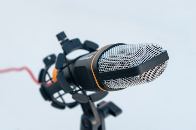 Closeup of a black and grey microphone on a white surface and background