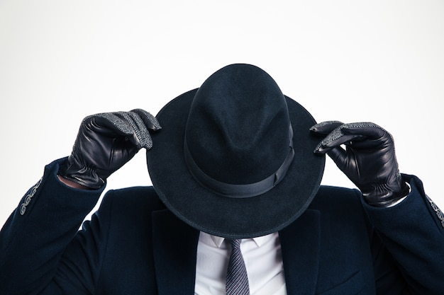 Closeup of black hat weared on business person in black suit and holded by modern black gloves over white wall