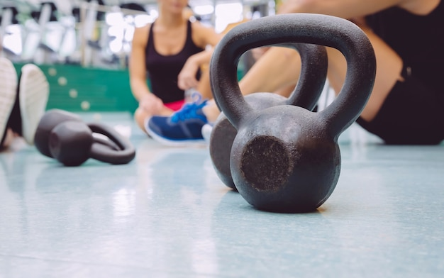 Closeup of black iron kettlebell and people group sitting on the floor of a fitness center in the background