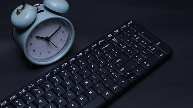 Черная клавиатура крупным планом с будильником на темном фоне
