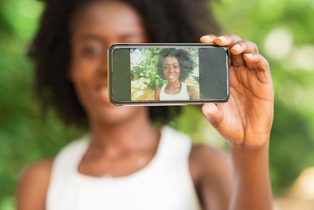Closeup of black lady taking selfie photo outdoors