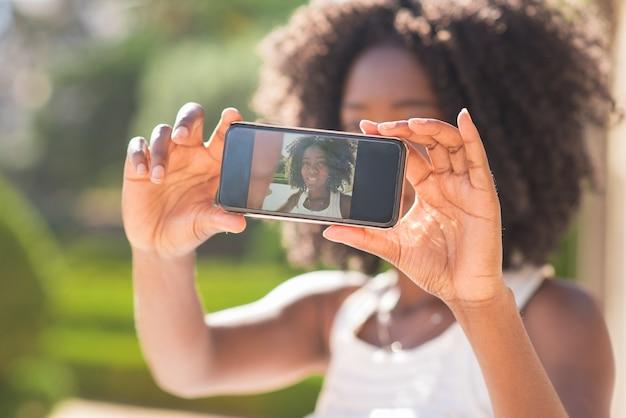 Closeup of black lady taking selfie photo in park
