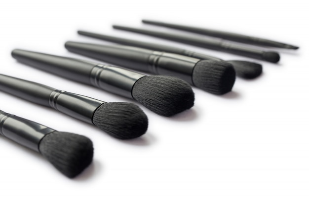 Closeup of black makeup brushes isolated on white space