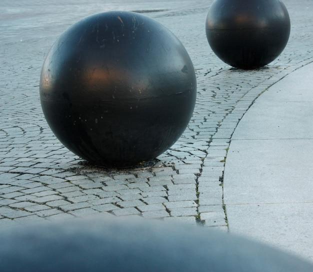 Primo piano delle palle rotonde nere su terra pietrosa