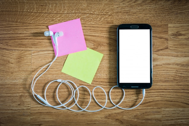 Closeup of black smartphone with white screen with headphones, sticky notes on wooden surface