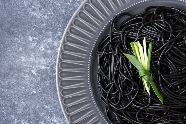 Closeup black spaghetti with ink cuttlefish with green leaf on gray plate on gray background with copy space, black pasta concept