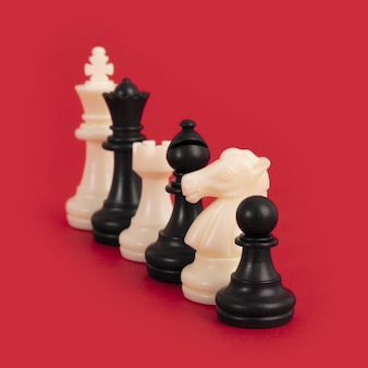 Closeup of black and white chess pieces lined up on a bright red