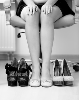 Closeup black and white conceptual photo of woman choosing most comfortable shoes