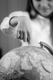 Closeup black and white image of cute girl pointing with finger at earth globe