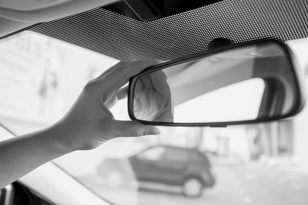Closeup black and white photo of female driver adjusting rear view mirror