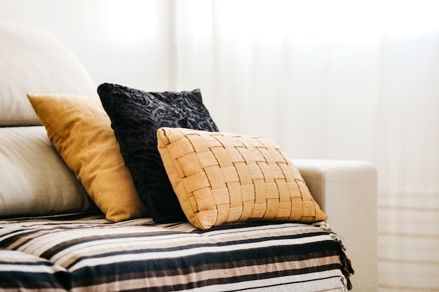 Closeup of black and yellow pillows on a white sofa