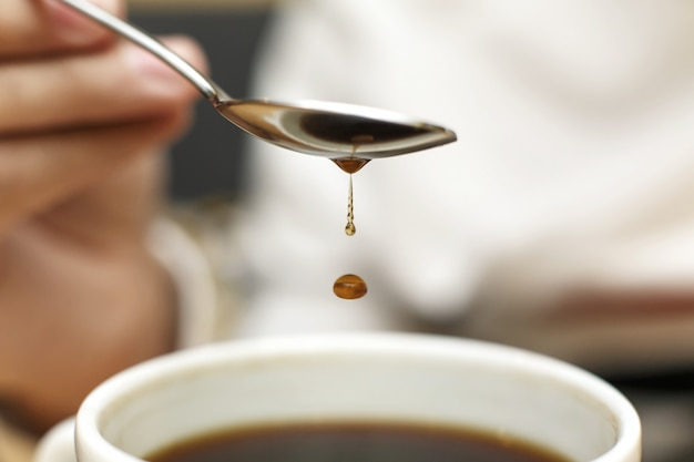 Closeup blob of coffee dripping from metal spoon into mug with coffee