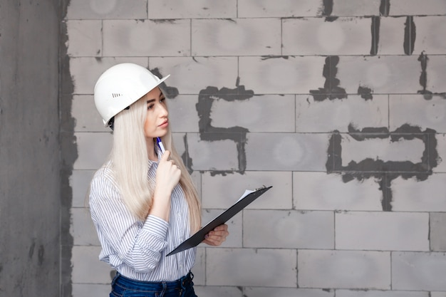 Closeup blonde girl foreman in white construction helmet holding pen, folder with plan in house under construction.