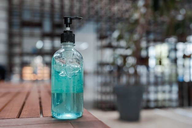Крупным планом синий спиртовой гель для дезинфицирующего средства для рук в прозрачной насосной бутылке на деревянном столе с фоном боке. новый нормальный. защита от заражения covid-19.