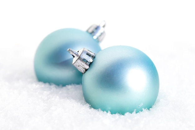 Closeup of blue christmas bulbs in the snow in front of a blurry background
