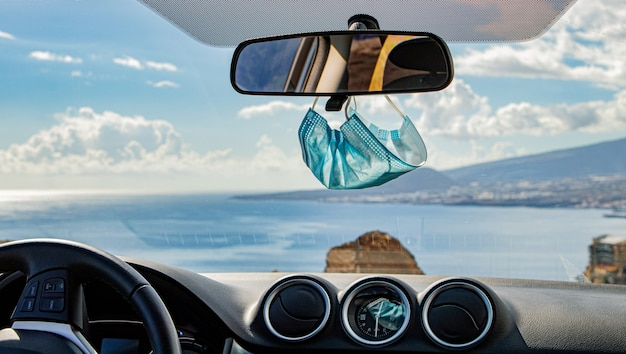 Closeup of a blue face mask hanging from the rearview mirror of a car on the road