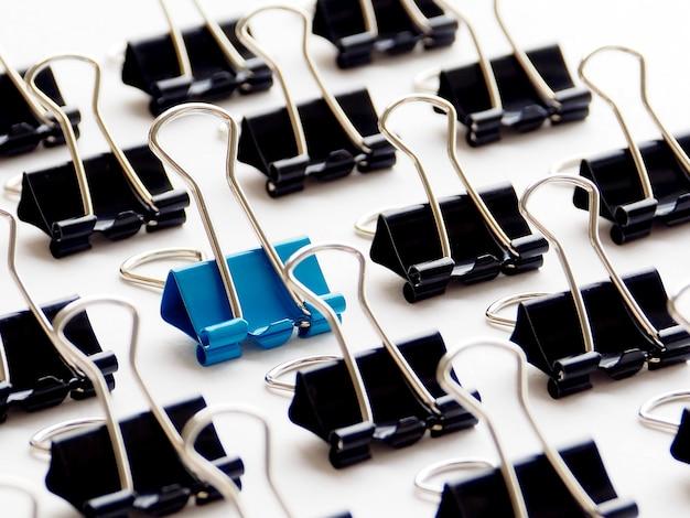 Closeup blue paper clip among black paper clips