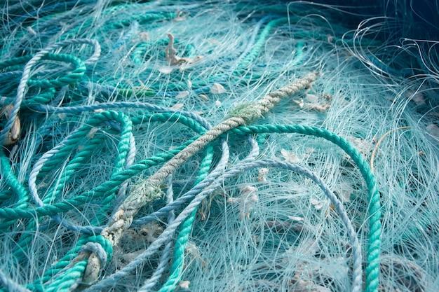 Primo piano di corde blu e reti da pesca l'una sull'altra sotto la luce del sole