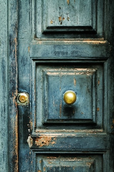 Closeup of blue turquoise old textured antique door with gold br