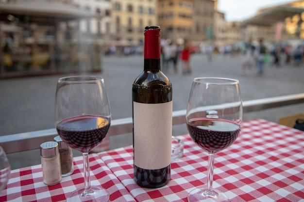 Closeup of bottle red wine and glasses on table of restaurant on background of piazza della signoria in summer day
