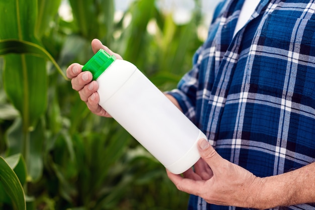 Closeup the bottle with chemical fertilizers in the hands of middle aged agronomist.