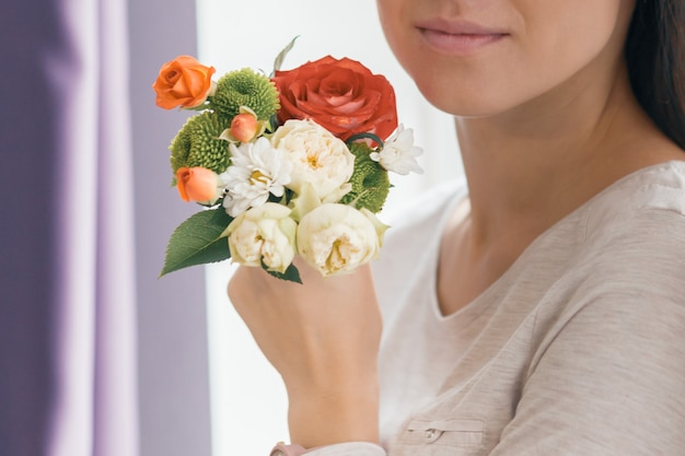Closeup of bouquet flowers in hand young smiling woman