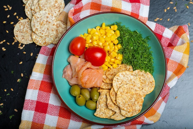 Closeup of a bowl of salad with salmon, crackers and vegetables on a napkin on the table