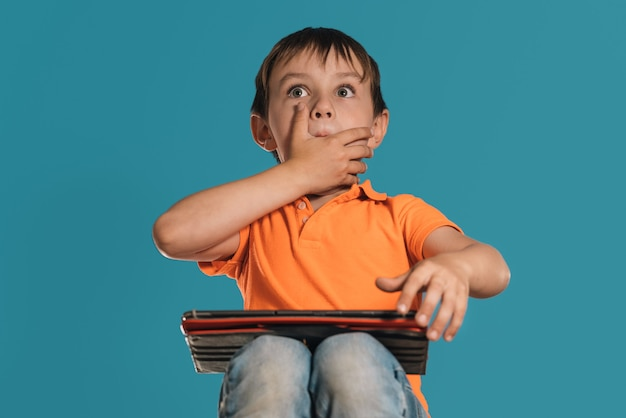 Closeup of a boy in an orange tshirt with a tablet on a blue background surprised expression