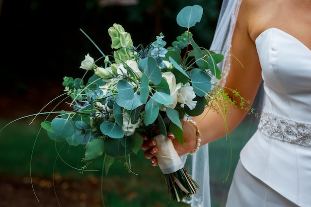 Closeup of bride hands holding beautiful wedding bouquet