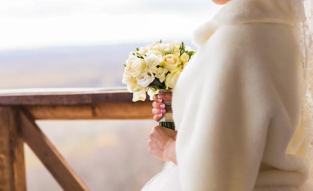Closeup of bride hands holding beautiful winter wedding bouquet.