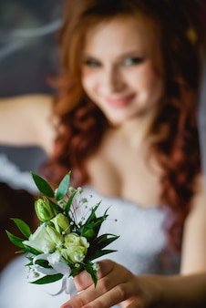 Closeup of a bride holding wedding boutonniere in the hands. in the morning, wedding day