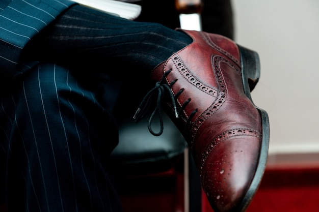 Closeup of a brogue shoe on a person sitting with crossed legs under the lights