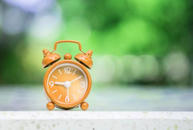Closeup brown alarm clock display 9 o'clock and 10 minutes