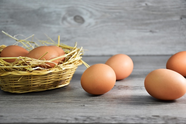 Closeup of brown chicken eggs/hen eggs in a wooden basket with rice hays and eggs
