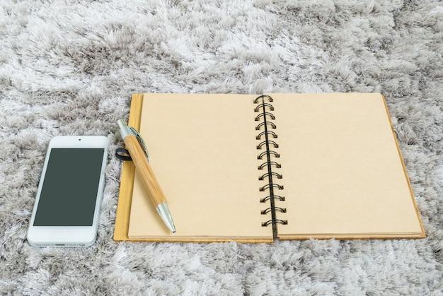Крупным планом коричневый блокнот, коричневая ручка и смартфон на фоне капет