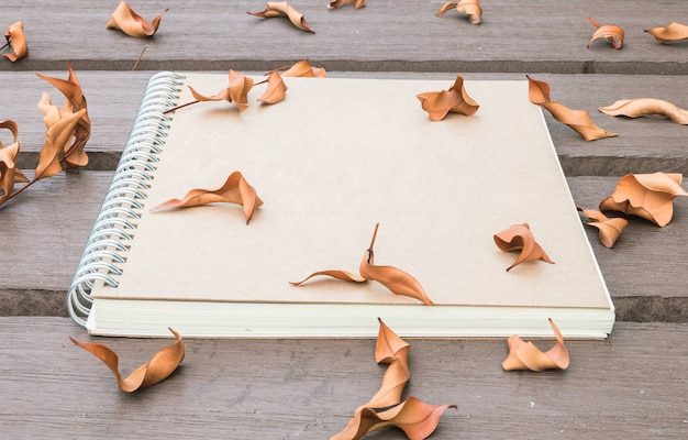 Closeup brown note book on wooden table in the garden with dried leaves textured
