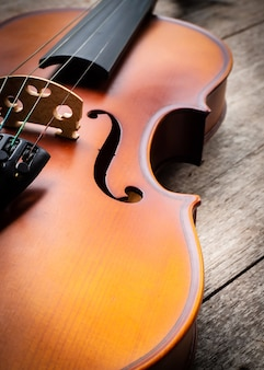Closeup brown violin on wooden background. art and music background.