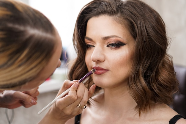 Closeup brunette young lady get ready for the event by makeup artist