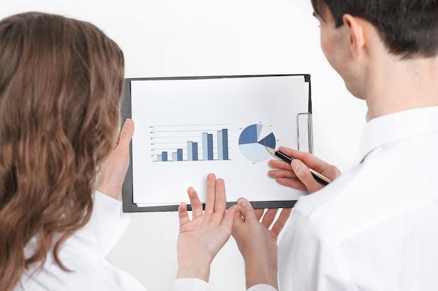 財務チャートについて話し合うcloseup.businessの同僚。ビジネスコンセプト