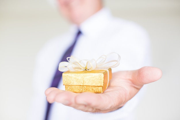 Closeup of business man giving small gift box