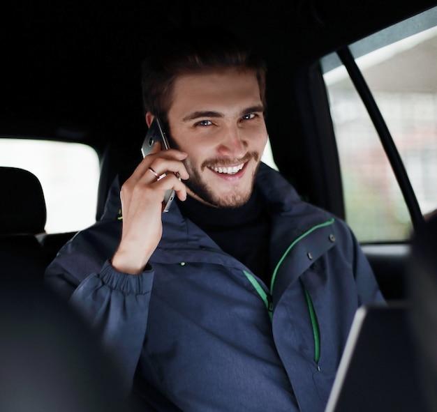 확대. 비즈니스 남자는 차에 앉아 노트북과 휴대 전화를 사용