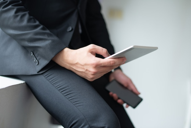 Closeup of business man using gadgets and leaning on sill