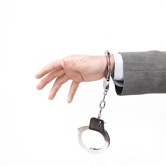 Крупным планом. деловых мужчин, держащих наручники. изолированные на белом