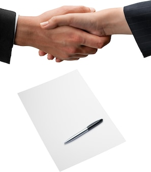 Closeup of business people shaking hands with contract on background