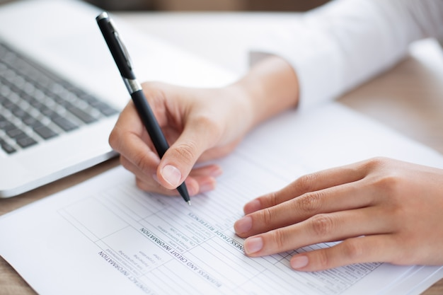 Closeup of business person completing form
