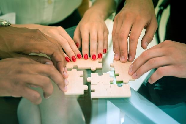 Крупным планом бизнес-команда, собирающая головоломку, сидя за столом