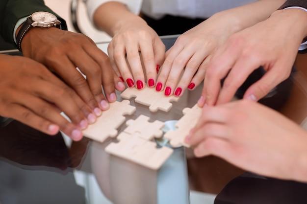 확대. 책상 뒤에 퍼즐 조각이 있는 비즈니스 팀