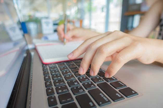 Primo piano di donna d'affari mano digitando sulla tastiera del computer portatile.
