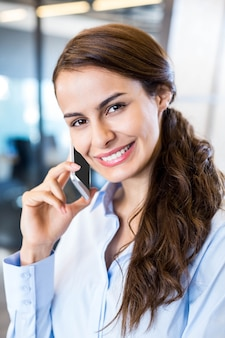 Closeup of business woman speaking on mobile phone in office
