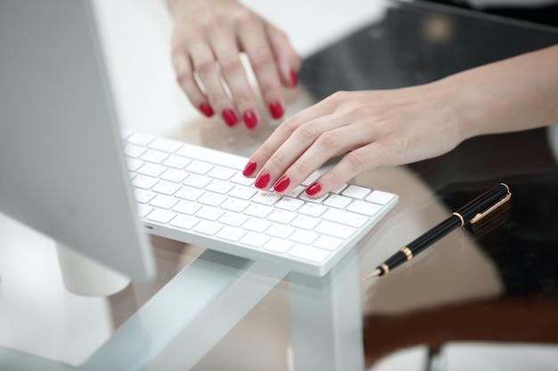 閉じる。コンピューターのキーボードでテキストを入力するビジネスウーマン